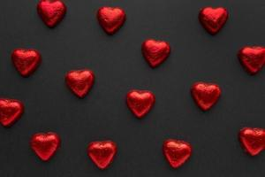 Corazones de chocolate rojo dispuestos sobre fondo negro foto