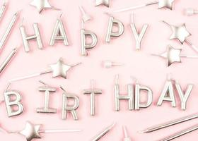 Happy Birthday candles on pink background