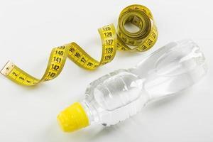 Cinta métrica amarilla y botella de agua sobre fondo blanco.