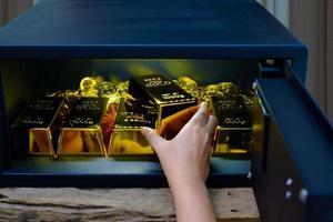 Caja fuerte de acero de apertura manual llena de lingotes de oro. foto