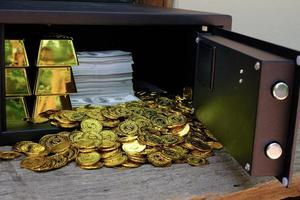 monedas de oro saliendo de la caja fuerte foto
