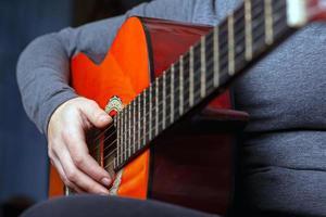 niña toca una guitarra acústica naranja con cuerdas de nailon foto