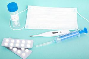 Test tube, syringe, pills and medical mask respirator, thermometer on blue background photo