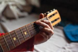 Guy plays a melody on an acoustic guitar while holding his hand on the fretboard photo