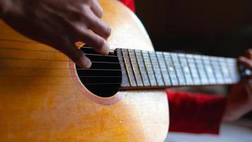 tocando una guitarra acústica con cuerdas de nailon foto