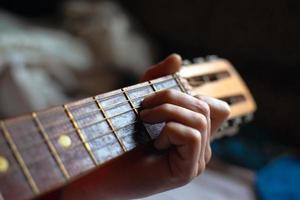 los dedos sostienen el acorde diapasón de la guitarra acústica foto