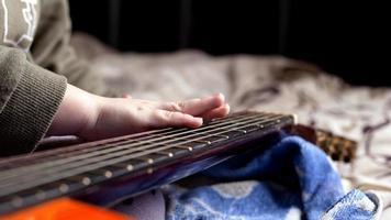 La mano del niño en el cuello de una guitarra acústica en color naranja, aprendiendo a tocar el instrumento. foto