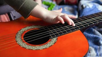 Child's hand touches the strings on an acoustic six-string guitar, earning to play a musical instrument
