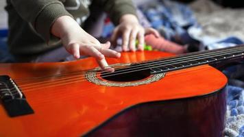 niño juega con cuerdas de guitarra acústica foto