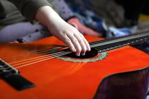 Child's hand pulls the strings on an orange acoustic guitar