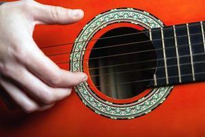 Los dedos tocan las cuerdas de una guitarra acústica clásica. foto