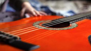 Child learns to play a musical instrument, the acoustic guitar photo