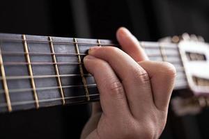 mano masculina abraza un acorde de guitarra acústica foto