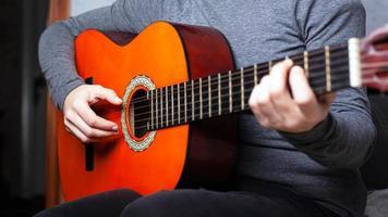 niña tocando una guitarra acústica naranja agarra el acorde en el diapasón foto