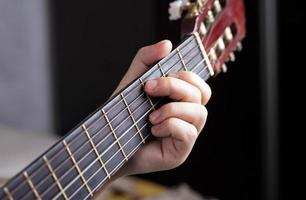 La mano del guitarrista aprieta los dedos sobre los acordes de una guitarra acústica. foto