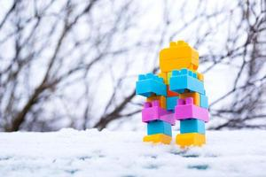 Toy robot in the snow, homemade little winter robot photo