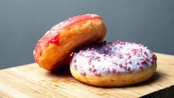 Sweet glazed donuts on wooden board photo
