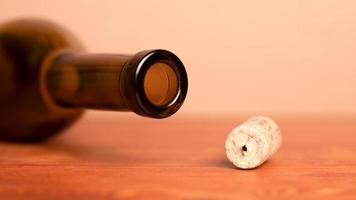 Wine cork and lying empty bottle on the table