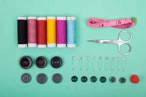 Sewing kit accessories with colorful threads, needles, pins, scissors on green background photo