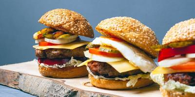 Assorted cheeseburgers on tree bark and gray background photo