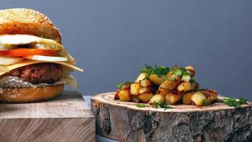 Gran hamburguesa jugosa con chuleta de queso, verduras y huevo sobre un fondo gris de cerca foto