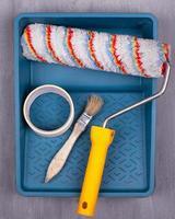 Suministros de pintura de colocación plana: rodillo, brocha, cinta adhesiva en una bandeja foto
