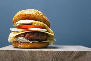 Jugosa hamburguesa con chuleta, queso y verduras sobre un fondo gris con espacio de copia foto