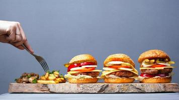Juicy burgers and potatoes with mushrooms on a gray background photo