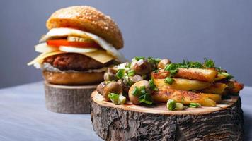 Fried potatoes with mushrooms and a juicy burger on forest wooden boards photo