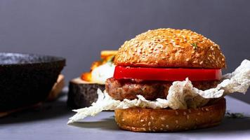 Homemade classic burger with chinese cabbage, juicy cutlet and sweet pepper on a gray background photo