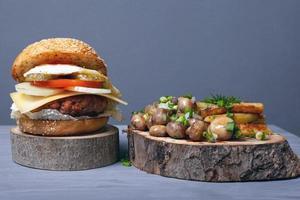 Jugosa hamburguesa de grasa, patatas fritas y champiñones con hierbas en bandejas de madera sobre fondo gris foto