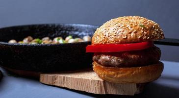 hamburguesa con jugosa chuleta, pan tierno y champiñones en una sartén de hierro fundido foto