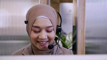 Beautiful woman in hijab at the computer with headset, distant work, call center. Confident islam woman worker in call center crossed arms face camera smiling joyful operator and helps with the order. video