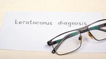 Gafas para visión con diagnóstico de inscripción de queratocono en primer plano de la mesa foto