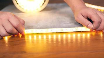 Manos instalan una tira de led luminosa de cerca sobre una superficie de madera foto