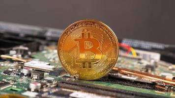 Moneda de oro bitcoin cryptocurrency a bordo de la computadora foto