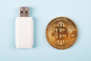Gold coin cryptocurrency bitcoin with USB stick close-up photo