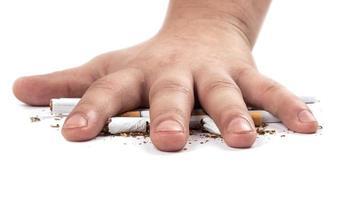 Fumador aplasta un cigarrillo con la mano sobre fondo blanco. foto