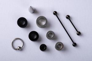 Joyería de oreja, túneles de oreja con dilatador y piercing apilados sobre fondo blanco. foto