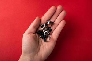 piercing y joyería para las orejas en la palma de la mano sobre un fondo rojo foto