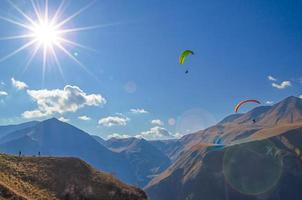 Paragliders and tourists on mountains with sun flare photo