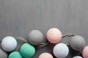 Bolas multicolores de hilo de color pastel sobre un fondo gris foto