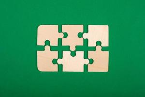 Wooden jigsaw puzzle on a green background photo