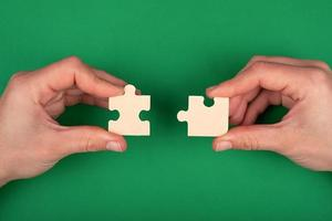 Hands of people connecting puzzles on a green background photo
