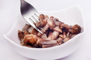 Small pickled mushrooms impaled on fork on white background photo