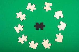 piezas del rompecabezas de colores blanco y negro, sobre un fondo verde foto