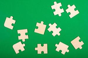 Piezas de un rompecabezas esparcidas sobre un fondo verde foto