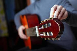 The musician tunes an acoustic six-string guitar photo