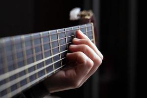 Female hand clamps a chord on an acoustic guitar photo