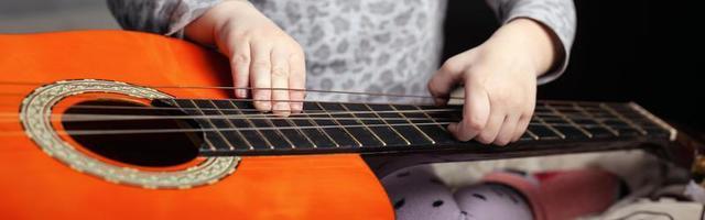 Guitar and small child, music themed panoramic shot photo